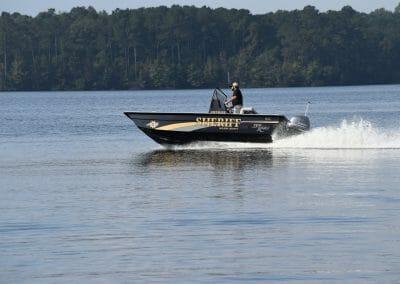 man driving a sheriffs boat side angle